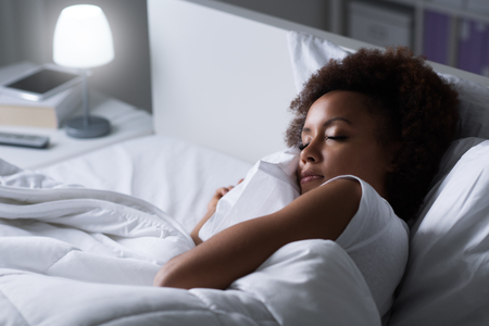 Young african woman sleeping in her bed at night, she is resting with eyes closed Stock Photo