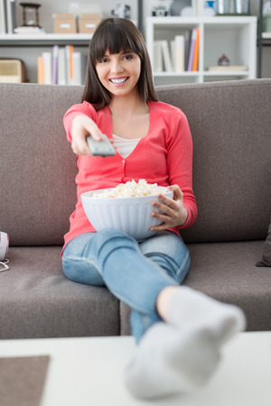 changing channel: Young smiling woman at home sitting on the couch and watching tv, she is holding a remote control and eating popcorn Stock Photo