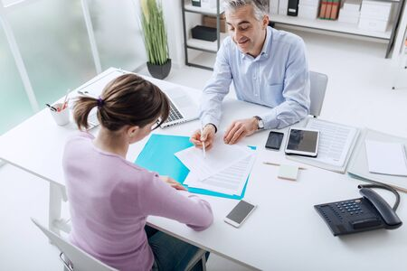 Confident advisor meeting with a customer in his office, he is explaining a contract document and policy to the woman sitting at his desk Stockfoto