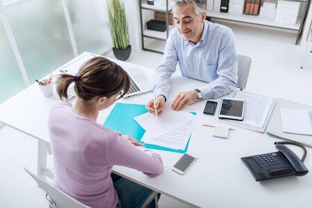 Zelfverzekerd adviseur ontmoeting met een klant in zijn kantoor, is hij het verklaren van een contract document en beleid om de vrouw, zittend aan zijn bureau Stockfoto