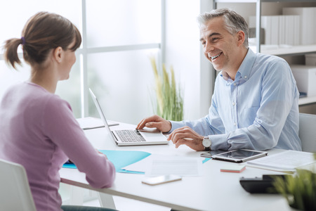 Confident advisor meeting with a customer in his office, he is explaining a contract document and policy to the woman sitting at his desk Standard-Bild