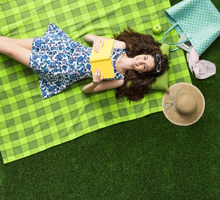grass beautiful: Cute girl relaxing outdoors on the grass and reading a novel book, she is smiling at camera