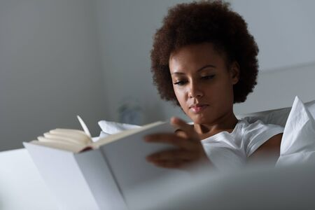 homey: Young african woman relaxing at home and reading a book, she is lying on the bed Stock Photo