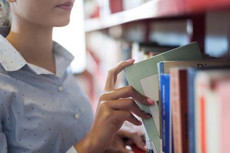 Vrouw bij de bibliotheek, is ze op zoek boeken op de boekenplank en het nemen van een boek op de plank, hand close-up Stockfoto
