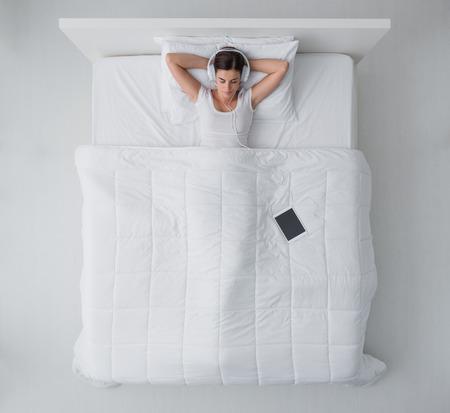 女性がベッドでリラックス、彼女はヘッドフォンを着ているとオンライン デジタル タブレットを使用して音楽を聴いて、トップ ビュー