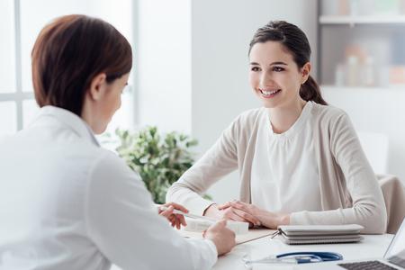 Glimlachende patiënt in het kantoor van de dokter, ze krijgt een voorschrift medicijn