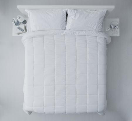 Elegante slaapkamer met witte dekbed en lakens, bovenaanzicht Stockfoto