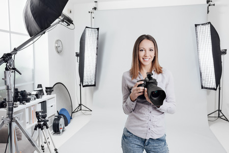 photographic camera: Young female photographer posing in the photo studio, she is smiling and holding a professional digital camera