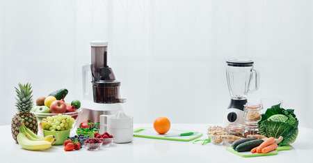 Kitchen table with fresh vegetables, fruit, seeds, blender and juicers; healthy diet and food preparation concept