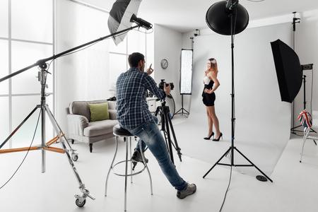 Jonge mooie vrouwelijke model poseren voor een fotoshoot in een studio, is een fotograaf fotograferen met een digitale camera Stockfoto