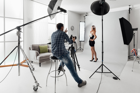 Young beautiful female model posing for a photo shoot in a studio, a photographer is shooting with a digital camera Stock Photo - 72066631