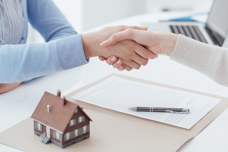 Real estate broker and customer shaking hands after signing a contract: real estate, home loan and insurance concept Stock Photo - 72044203