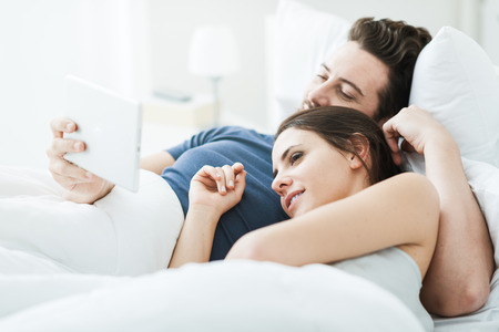 Young happy couple relaxing in bed and connecting with a touch screen tablet, they are enjoying and watching a movie together