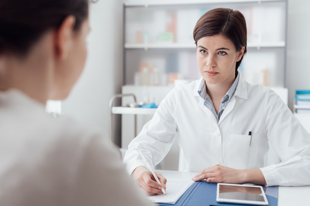 prescription medicine: Female doctor meeting with a patient in the office, she is giving a prescription to the woman, healthcare and medicine concept