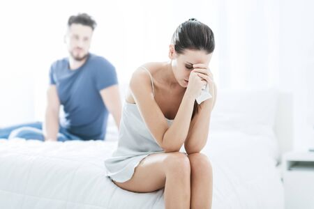 Young couple in the bedroom, the woman is sitting alone and crying, relationship difficulties concept Stock Photo