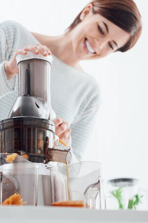 Young smiling woman using a juice extractor and preparing an healthy smoothie using fresh organic vegetables and fruit