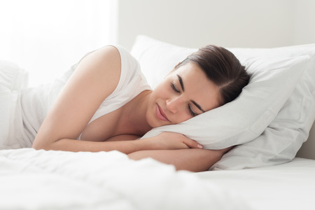 sleepiness: Beautiful smiling woman lying down in bed and relaxing, she is sleeping with eyes closed Stock Photo