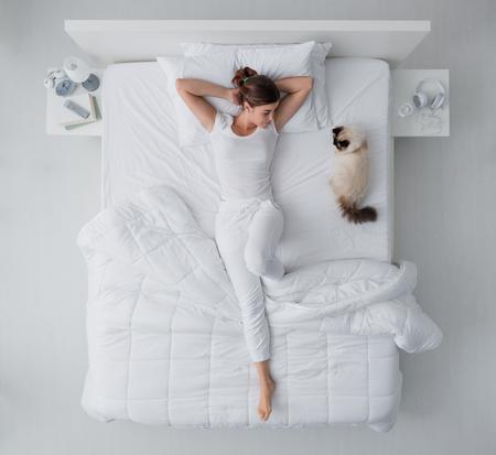 젊은여자가 그녀의 아름 다운 birman 고양이, 상위 뷰와 함께 침대에 누워