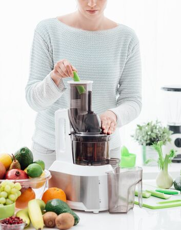 Woman using a juice extractor and preparing an healthy detox drink with celery and other greens