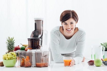 Smiling young woman drinking healthy juice made with fresh vegetables and fruits, she is using a juice extractor Stockfoto