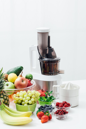 Fresh organic fruit, juicer and juice extractor on a table; healthy eating and nutrition concept