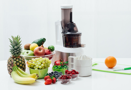 Fresh organic fruit and juicers on a table, healthy eating and nutrition concept
