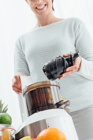 Woman using a juice extractor and preparing healthy drinks using fresh vegetables and fruit, she is holding the auger Stock Photo