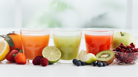 Glasses with fresh colorful juices and organic fruit, healthy diet and nutrition concept Foto de archivo