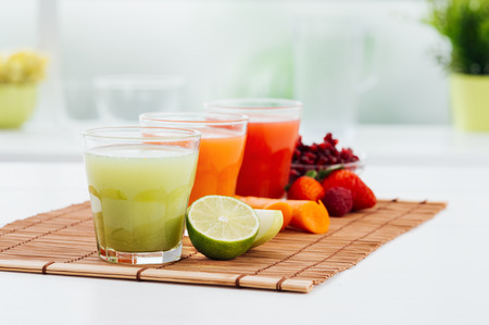 natural juices: Colorful juices and their natural ingredients: green apple and lime, carrot, strawberries and pomegranate: healthy diet concept Stock Photo