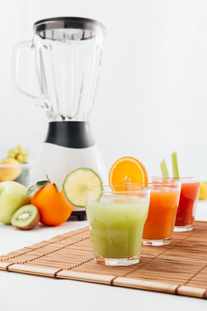 kitchen appliances: Healthy fresh fruit juices and blender on the kitchen table, healthy eating concept Stock Photo