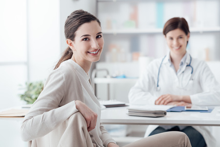 Smiling patient receiving a medical consultation and looking at camera, the female doctor is sitting at desk on the background