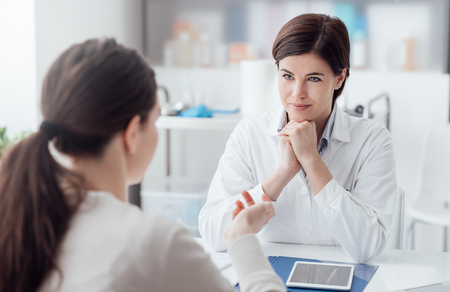 Doctor working in the office and listening to the patient, she is explaining her symptoms, healtcare and assistance concept