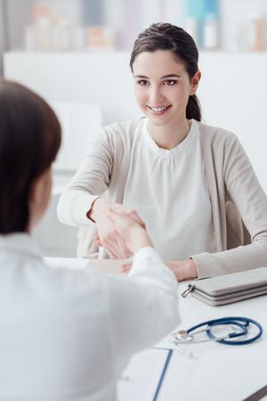 Vrouwelijke arts en jonge lachende patiënt in het kantoor, ze schudden handen