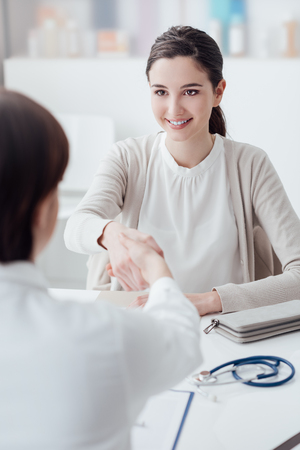 Female doctor and young smiling patient in the office, they are shaking hands Standard-Bild