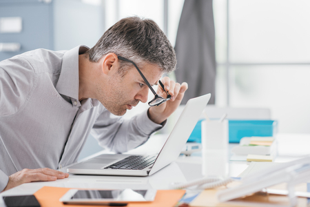 Der Geschäftsmann, der am Schreibtisch arbeitet, er starrt oben auf den Laptopschirmabschluß und hält seine Gläser, Arbeitsplatzvisionsprobleme Standard-Bild