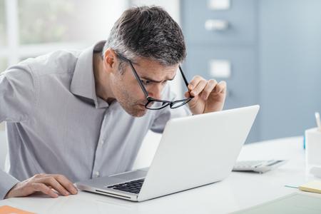 Der Geschäftsmann, der am Schreibtisch arbeitet, er starrt oben auf den Laptopschirmabschluß und hält seine Gläser, Arbeitsplatzvisionsprobleme