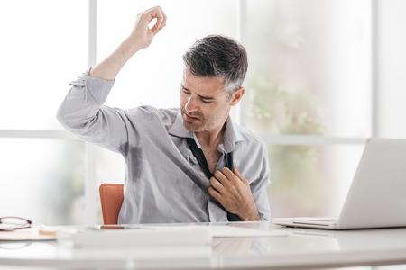Zenuwachtige zakenman die op het kantoor werkt, hij zweet en controleerde zijn oksels Stockfoto