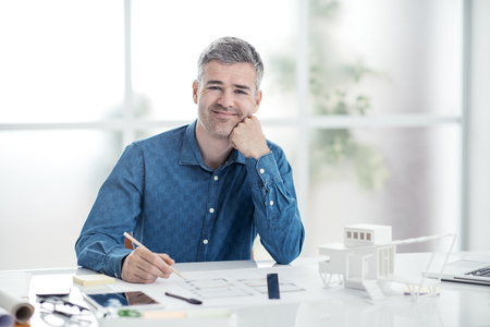 Professional architect sitting at office desk and working, he is checking a project blueprint, engineering and architecture concept Stock Photo