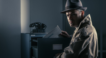 Vintage undercover spy stealing files in a filing cabinet late at night, security, data theft and crime concept Stock Photo