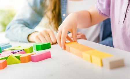 Meisje het spelen met kleurrijke stuk speelgoed houtsneden, haar moeder helpt haar, onderwijs en pretconcept Stockfoto
