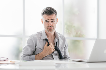 Nervous businessman working in a very hot office, he is sweating and loosening his tie Stock Photo