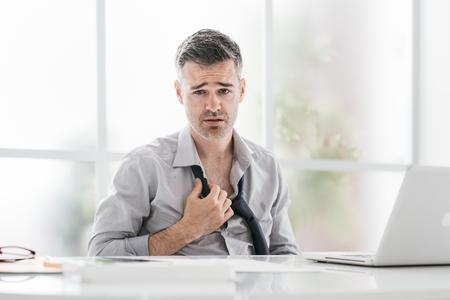 Zenuwachtige zakenman die in een zeer heet bureau werkt, zweet hij en maakt zijn band los