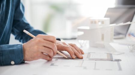 Professioneller Architekt arbeitet am Schreibtisch, er zeichnet und macht Messungen an einem Projekt Blueprint, Engineering und Architektur-Konzept Standard-Bild - 85247215