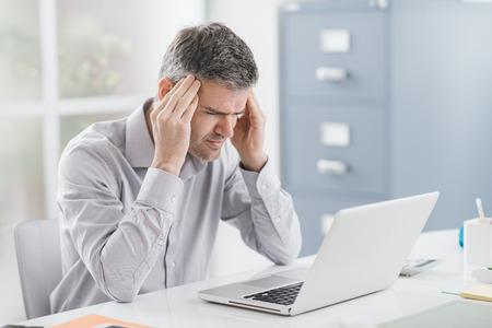 Beklemtoonde zakenman die bij bureau werkt en een hoofdpijn heeft, raakt hij zijn tempels