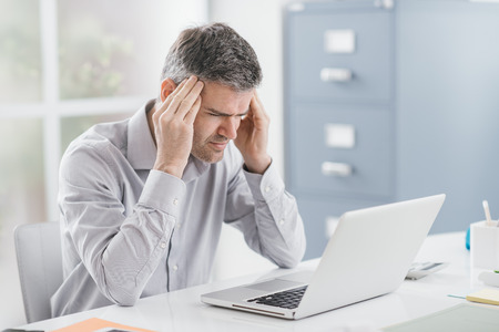 Der betonte Geschäftsmann, der am Schreibtisch arbeitet und Kopfschmerzen hat, berührt er seine Tempel Standard-Bild - 88364391