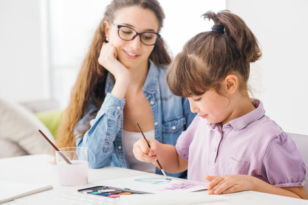 Cute preschool girl painting at home with watercolors, her mother is helping her