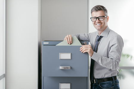 Businessperson at work: professional confident office clerk searching files in the filing cabinet
