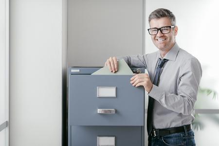 Ondernemer op het werk: professionele zelfverzekerde kantoorbediende die bestanden zoekt in de archiefkast