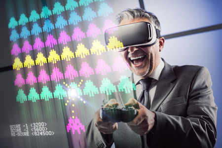Businessman enjoying virtual reality gaming, he is wearing a VR headset and playing with a videogame controller Stock Photo