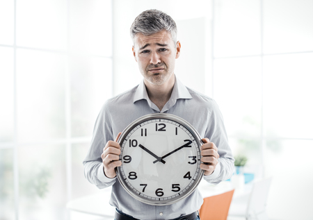 Business, time management and deadlines: sad businessman holding a clock, he is missing a deadline